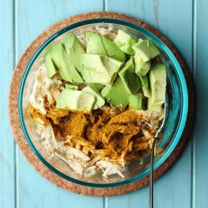 Curried Avocado Chicken Salad in clear bowl with blue teal background
