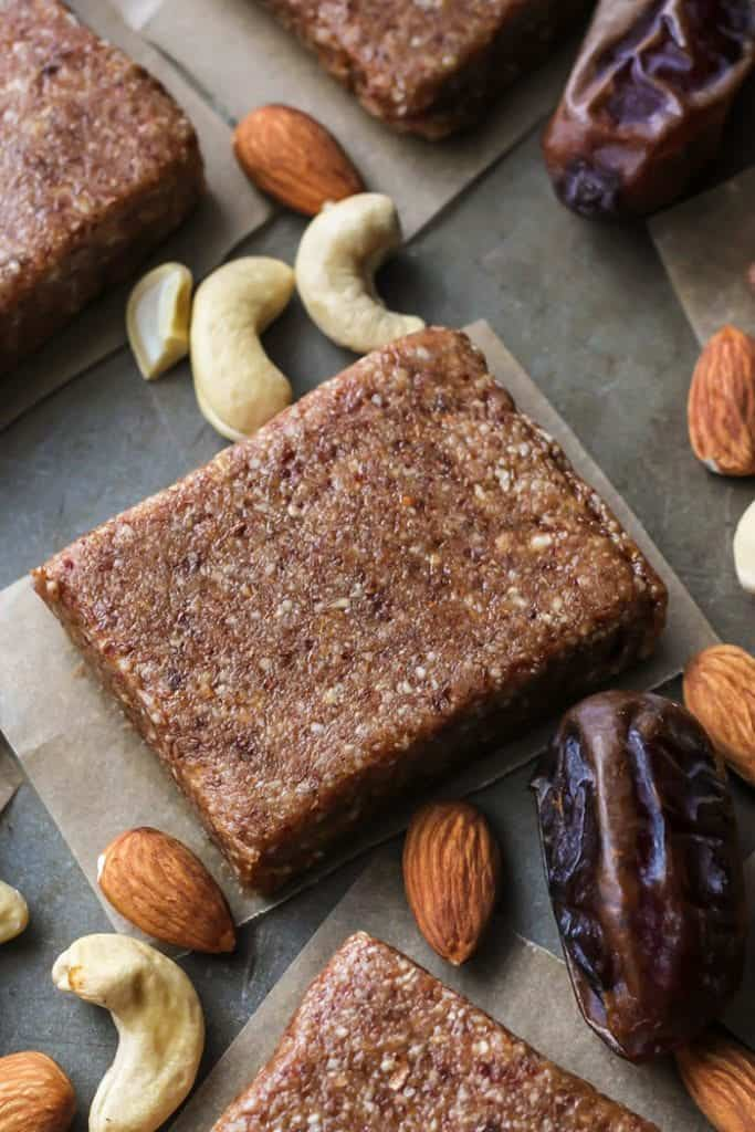 up close 4-ingredient homemade protein bar on pan with parchment paper, cashews, almonds and medjool dates