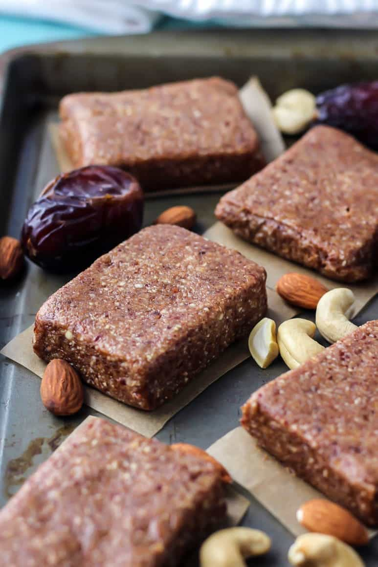 4-ingredient homemade protein bars on pan with cashews, almonds and dates