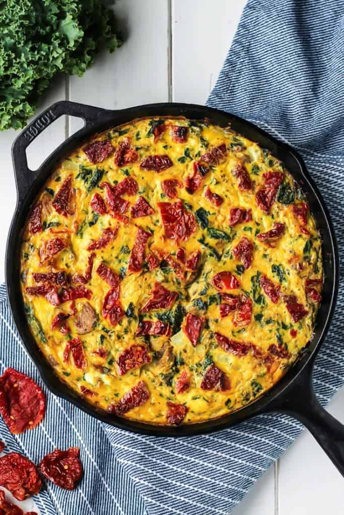 egg and sausage frittata recipe with spaghetti squask in cast iron skillet on blue striped towel