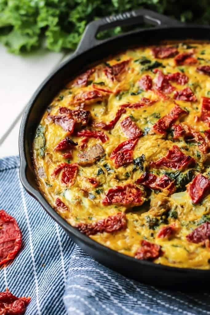 easy italian sausage frittata recipe in cast iron skillet on blue striped towel