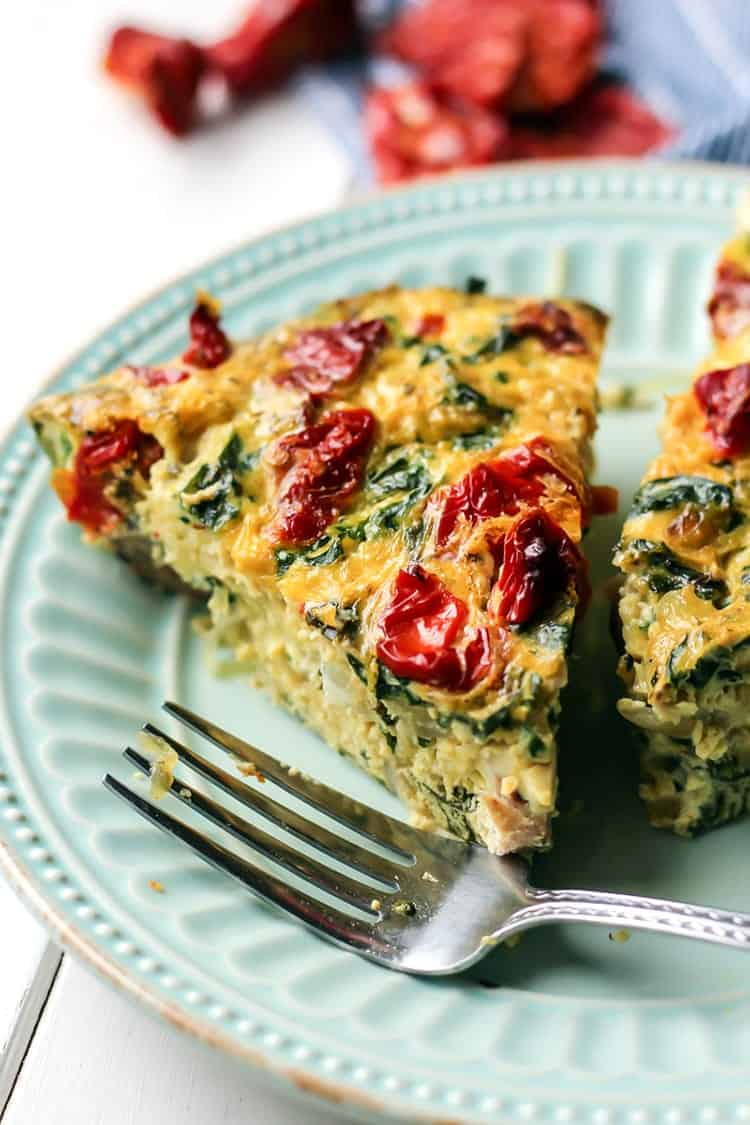 Sausage Kale Spaghetti Squash Frittata with Sun-Dried Tomatoes on teal plate with fork