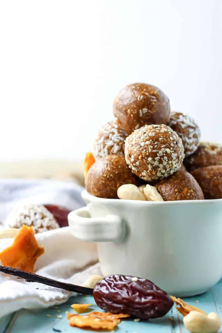 Energy balls with mango cashews dates and vanilla bean in white bowl