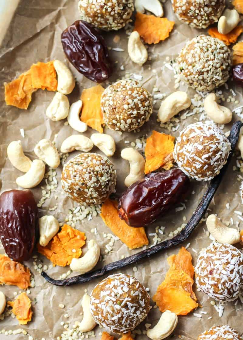 Mango Vanilla Bean Energy Balls with dates and cashews on parchment paper