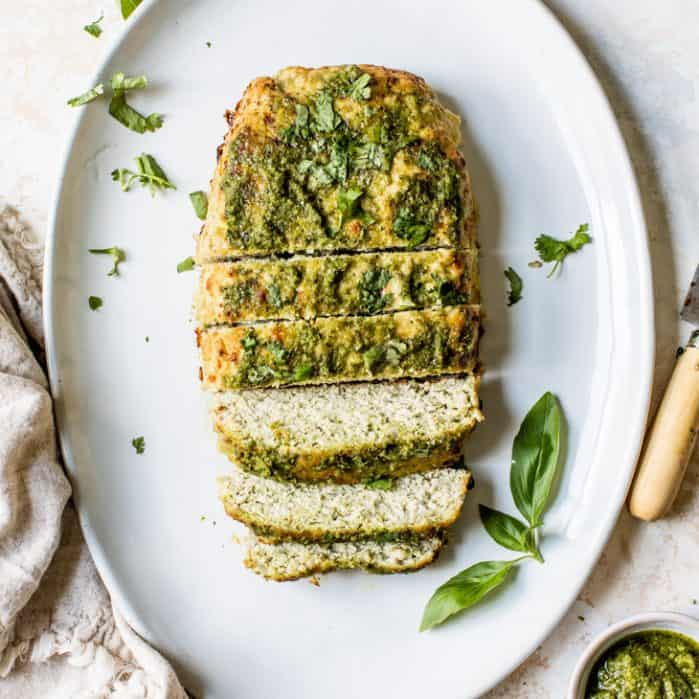 sliced pesto turkey meatloaf on platter with fresh basil