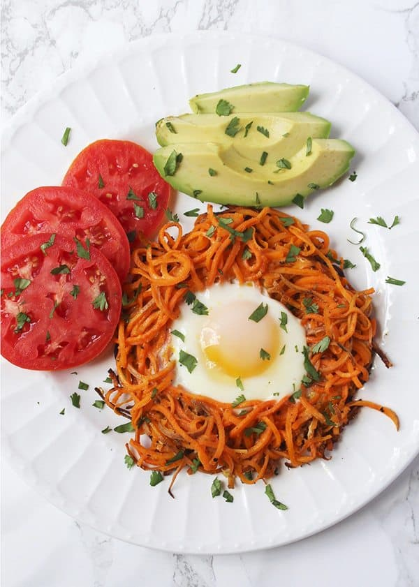 Spirazlied Sweet Potato Egg in a Hole with tomatoes and avocado on white plate and marble