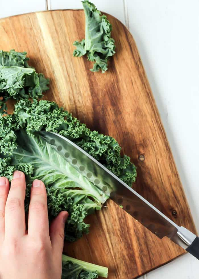 chopping kale for kale chips with knife on cutting board