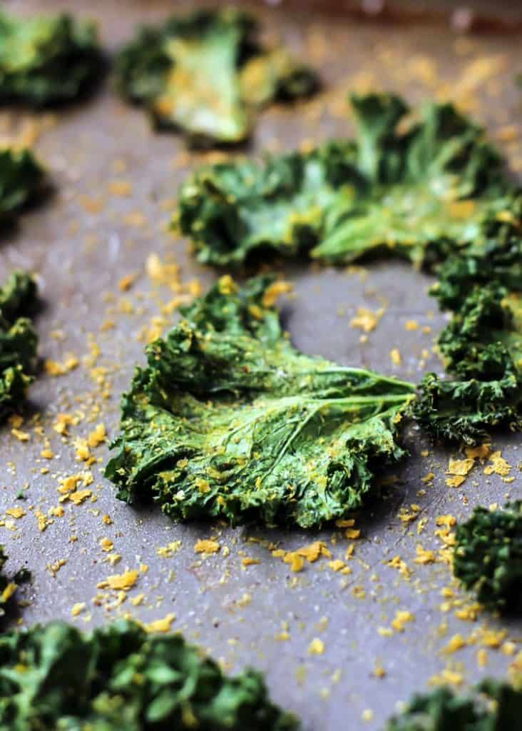 close up of kale chips on baking sheet with seasoning