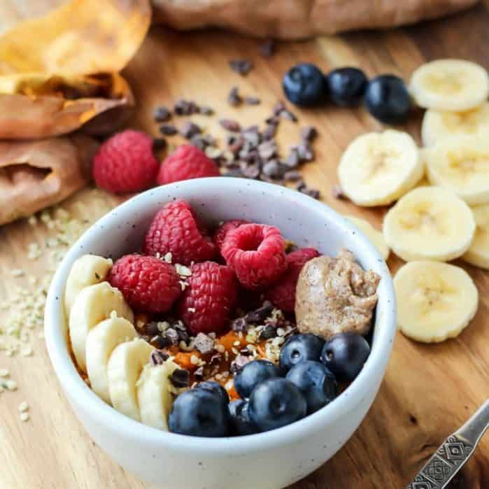 whole 30 protein breakfast bowl in white dish with bananas raspberries blueberries on cutting board