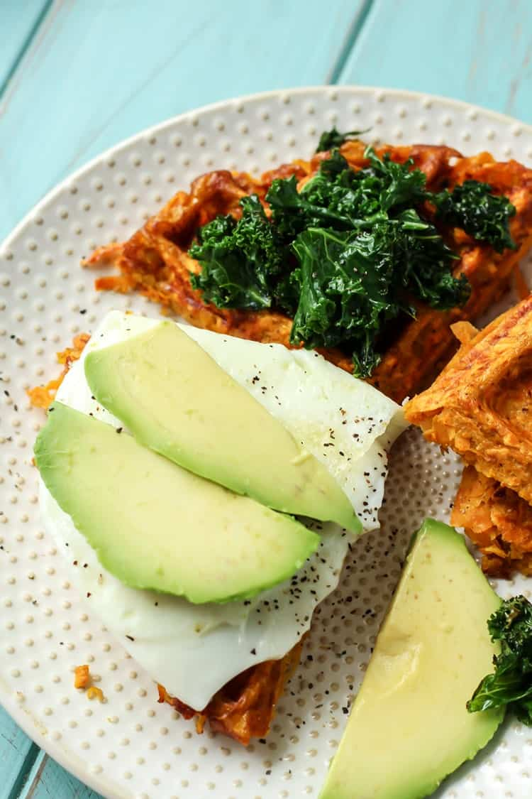 Paleo Sweet Potato Waffle Breakfast Sandwich with avocado and kale on white plate