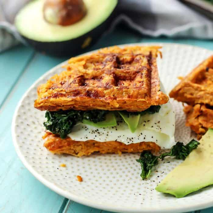 Sweet Potato Waffle Breakfast Sandwhich on white plate with avocado