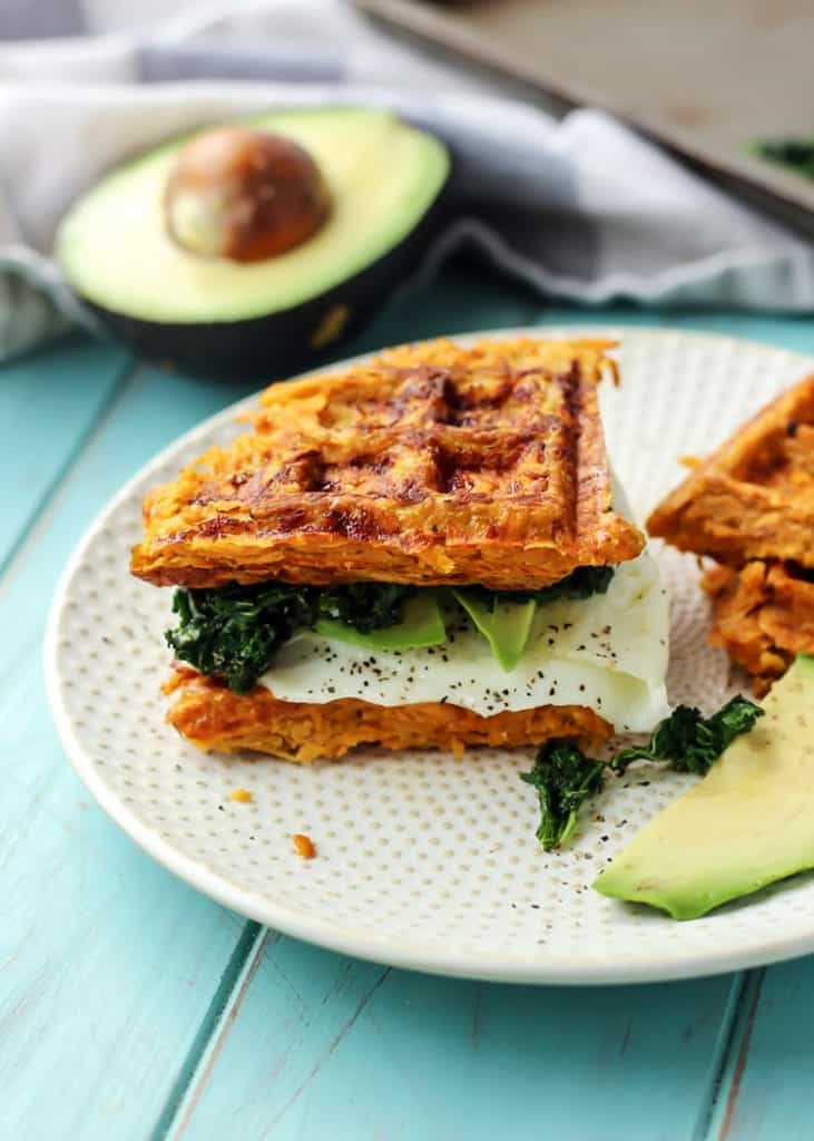sweet potato waffle breakfast sandwich on plate with avocado and kale