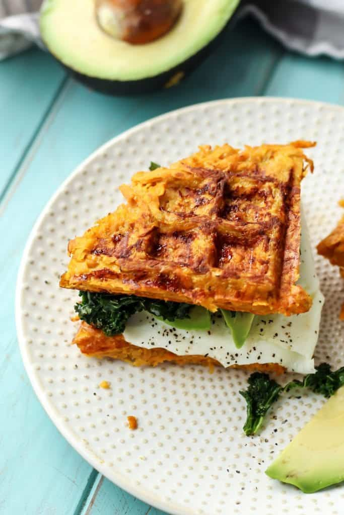 Paleo Sweet Potato Waffle Breakfast Sandwich on white plate with avocado kale and egg with pepper