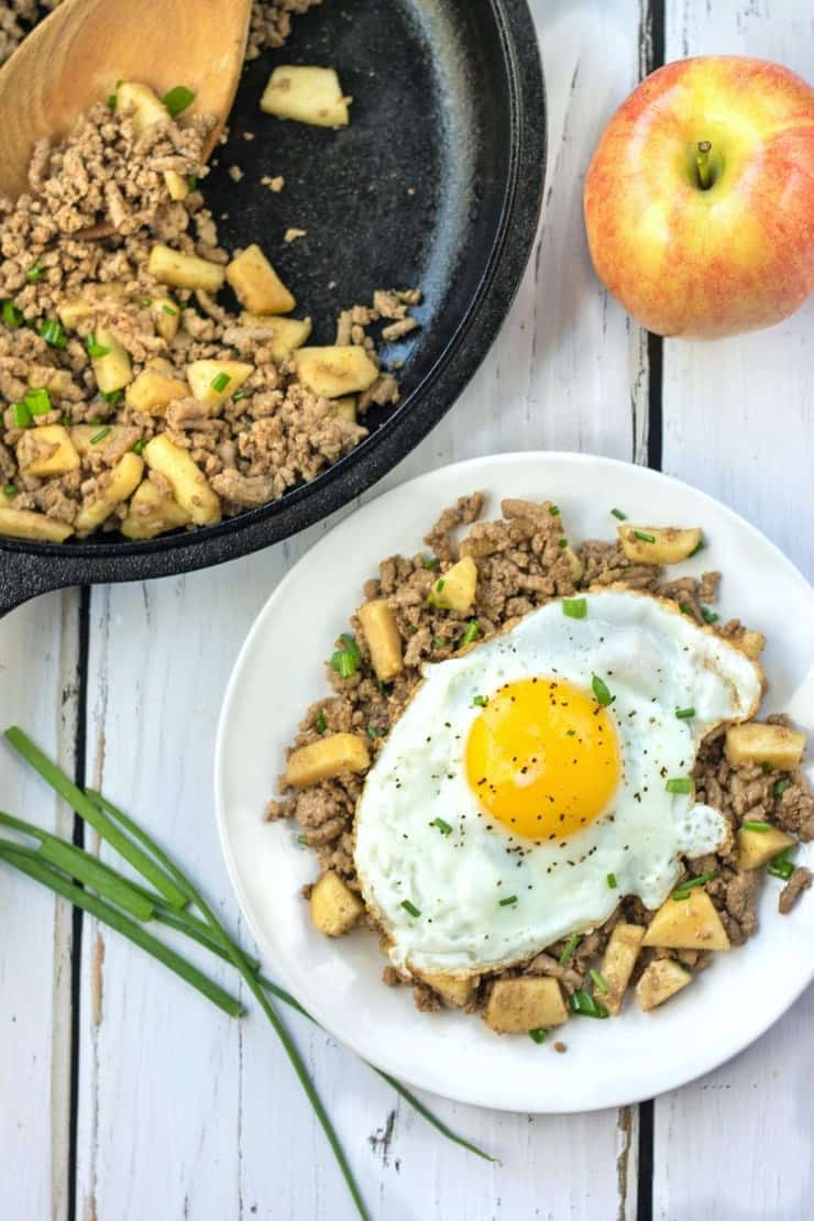 Balsamic Turkey Hash with fried egg in cast iron skillet and white plate with apple and green onion