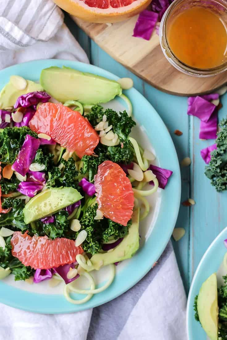 Grapefruit Zucchini Noodle Kale Salad with avocado on blue plate