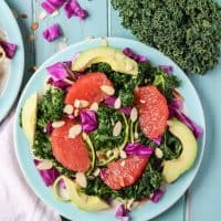 Grapefruit Zucchini Noodle Kale Salad, plus a super easy ginger grapefruit vinaigrette with avocado on blue plate