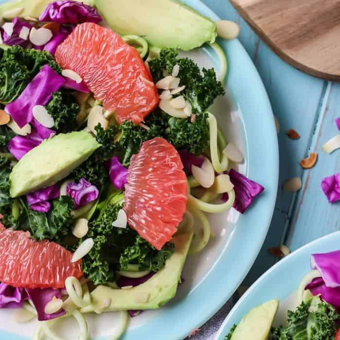 Grapefruit Zucchini Noodle Kale Salad, plus a super easy ginger grapefruit vinaigrette and avocado on blue plate