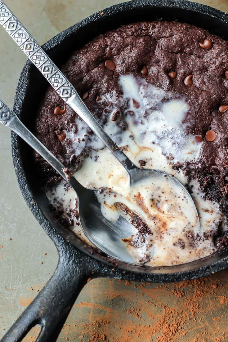 Skillet Brownie with melted vanilla ice cream and spoons