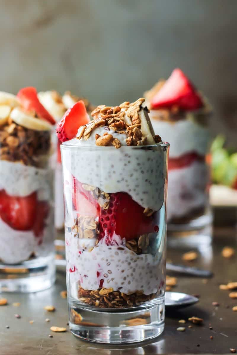 Strawberry Banana Chia Seed Pudding Parfaits layered in clear cups with granola