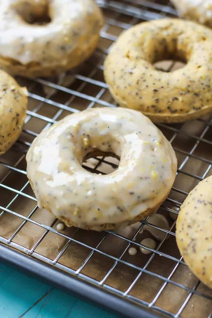 Glazed Lemon Poppy Seed Donuts on drying rack