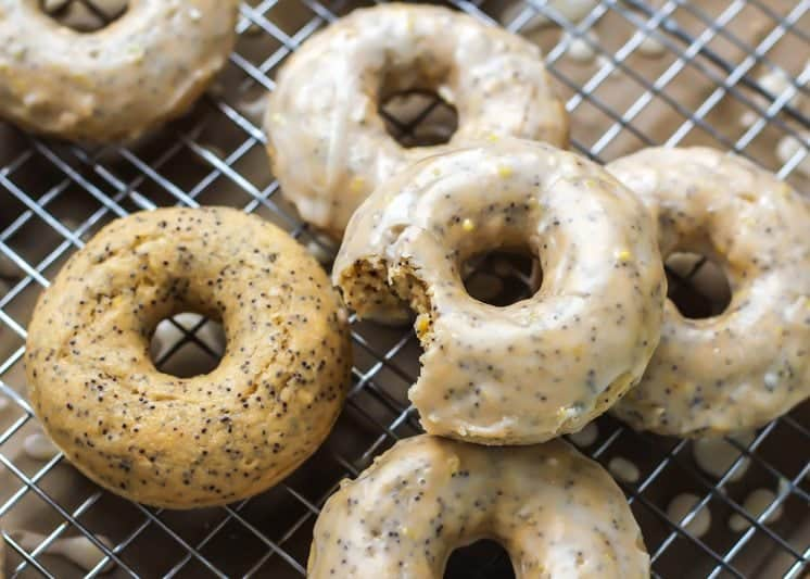 lemon poppy seed donuts with bite taken out on drying rack