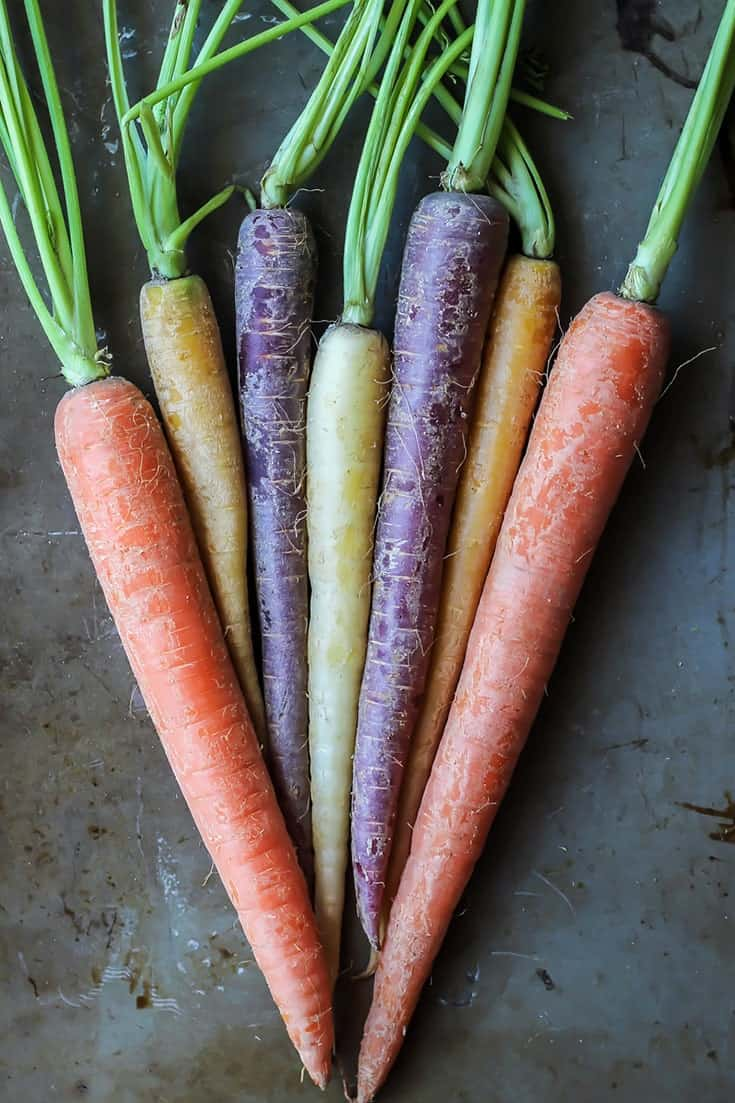 whole rainbow carrots with stems on baking sheet