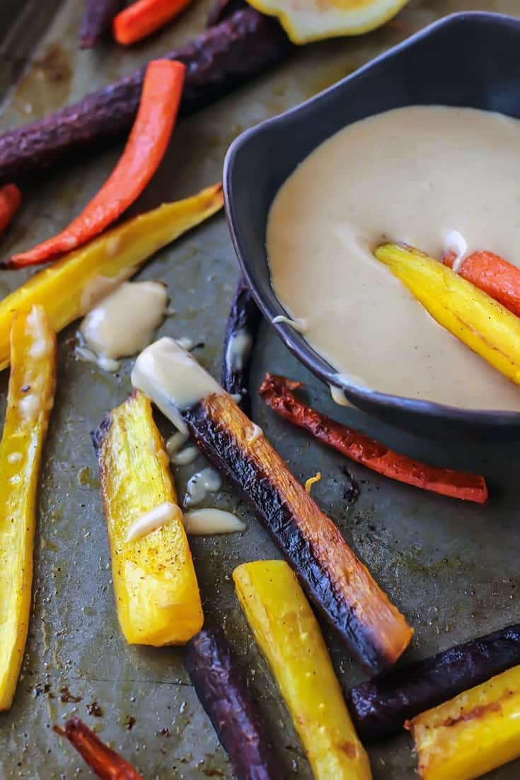 Roasted Rainbow Carrots dipping into tahini ginger sauce