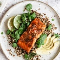 glazed salmon on plate of quinoa with avocado and citrust