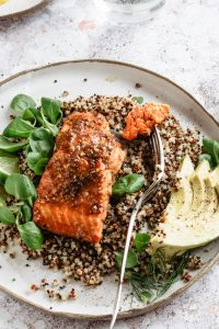 plate with fork and glazed salmon on quinoa