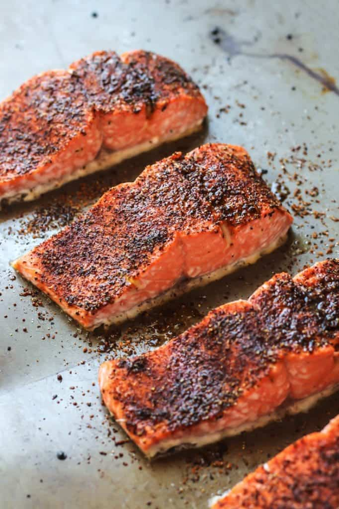 Sweet & Spicy Glazed Salmon cooked and cut on baking sheet