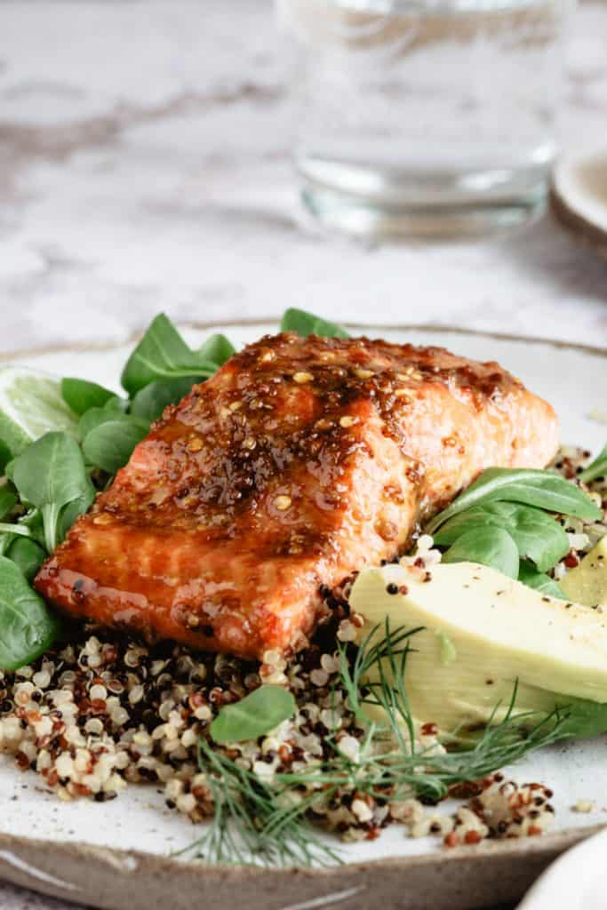up close glazed salmon fillet with quinoa and greens