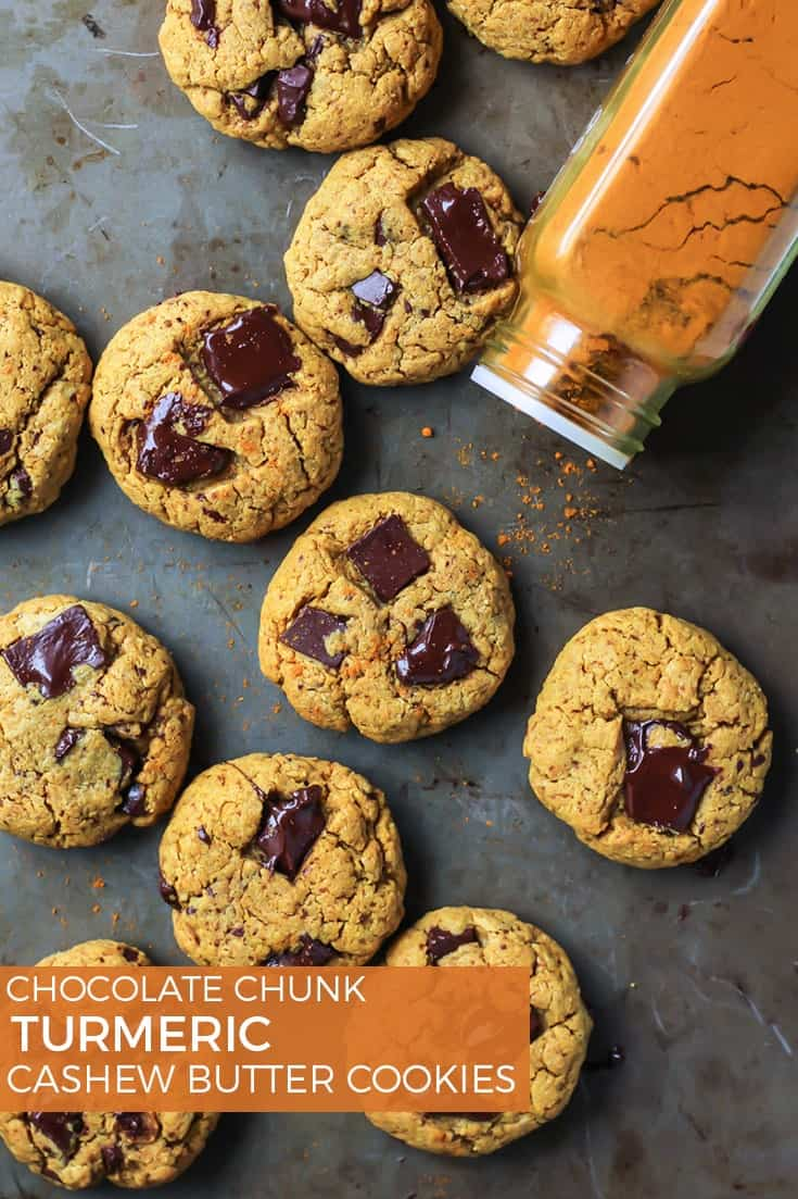 Chocolate Chunk Turmeric Cashew Butter Cookies with tumeric spice shaker on cookie sheet