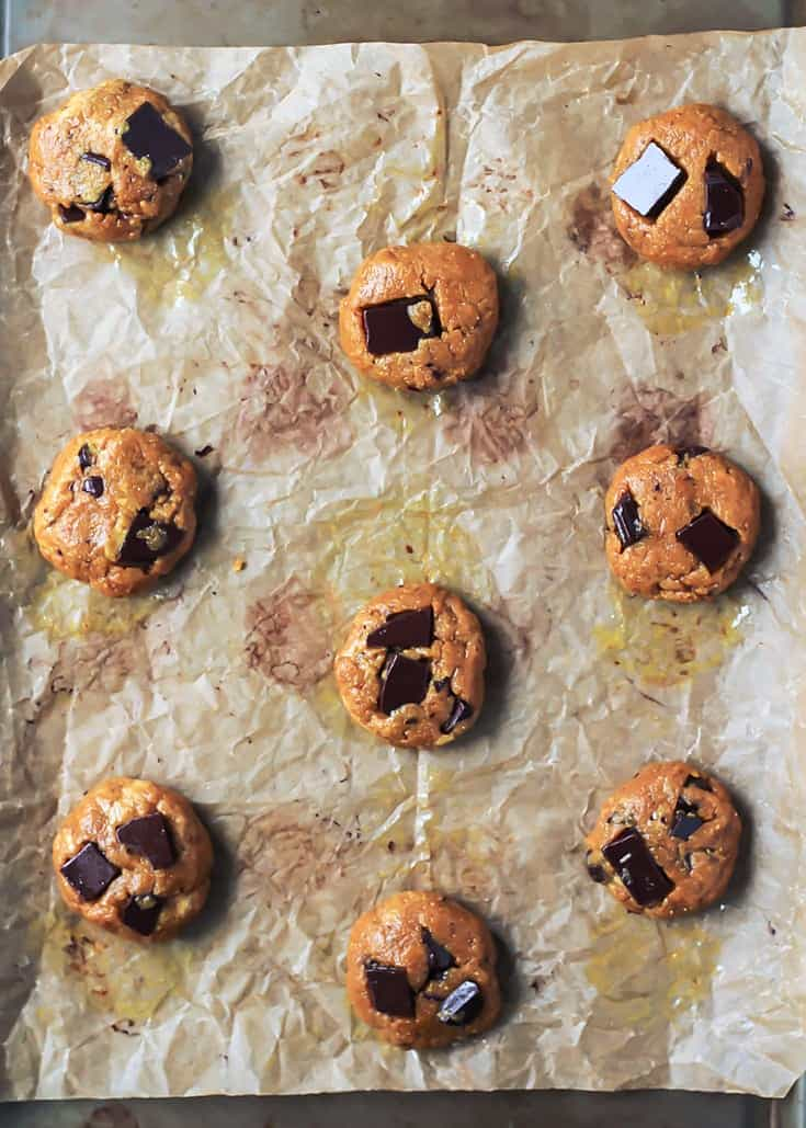 Chocolate Chunk Turmeric Cashew Butter Cookie dough balls on parchment paper