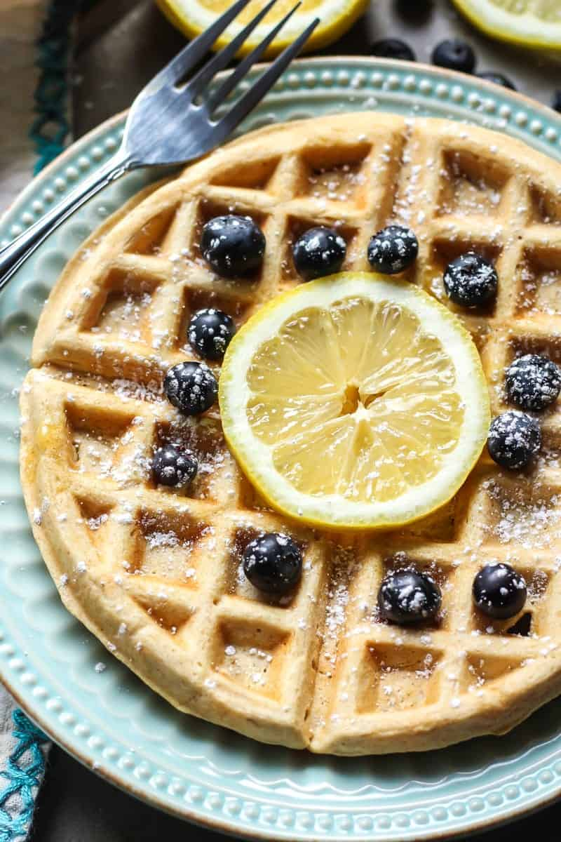 lemon blueberry waffles with sprinkled powdered sugar on blue plate with fork