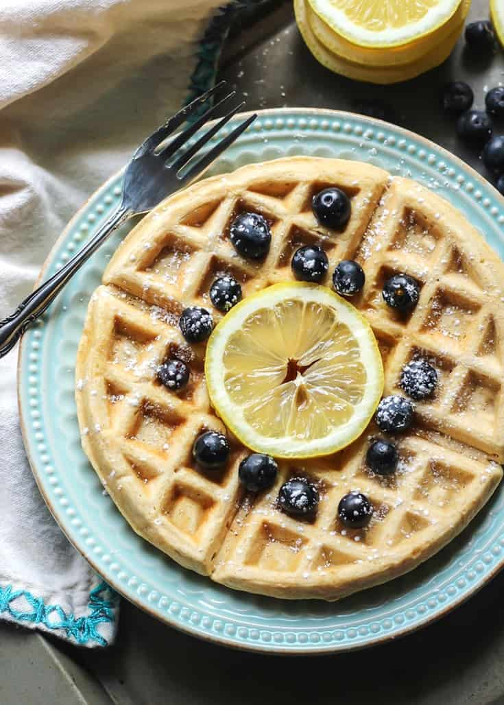 waffles with lemon slice and blueberries on blue plate with fork