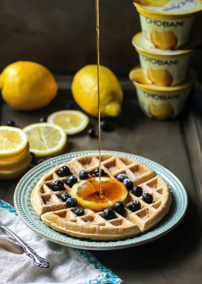 syrup poured on lemon blueberry waffles on blue plate with chobani yogurt