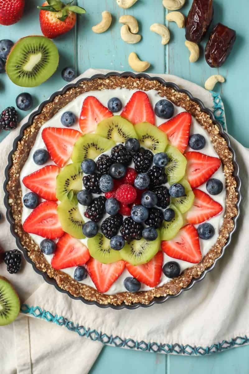 Greek Yogurt Fruit Tart with superfood crust topped with blueberries, strawberries, kiwi, blackberries, raspberries and cashews