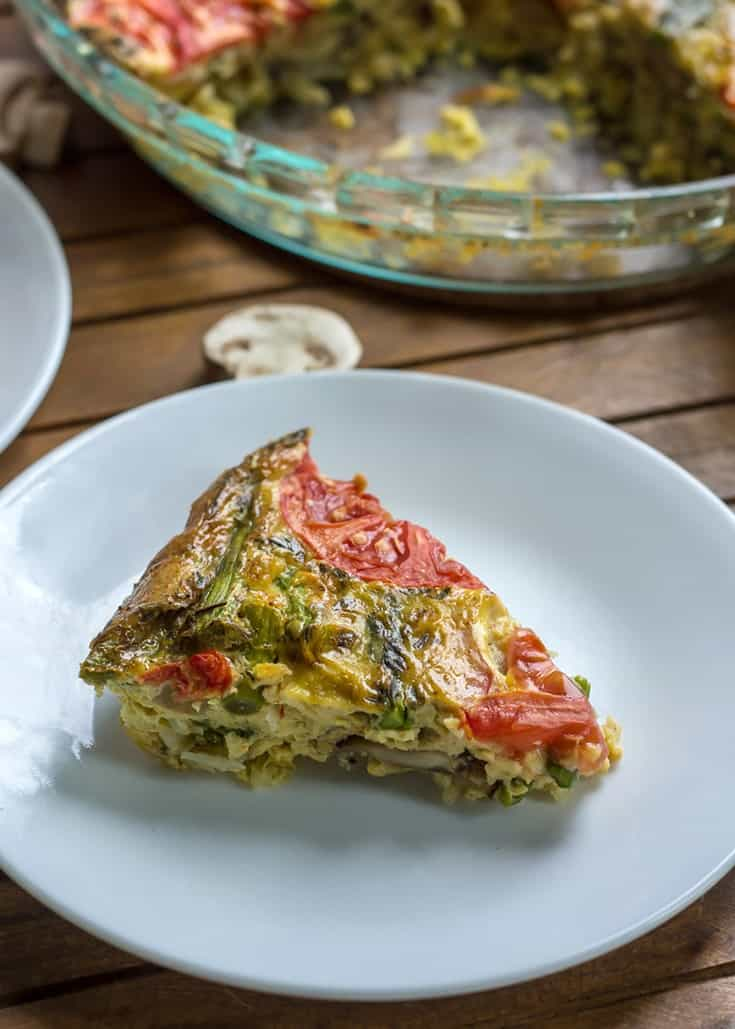 Mushroom Asparagus Crustless Quiche with shredded potato, and topped with tomatoes. Gluten-free, dairy-free, and paleo.
