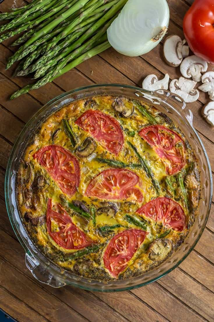 crustless quiche with asparagus, mushroom, onion, tomato in clear pie plate