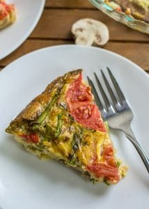 Mushroom Asparagus Crustless Quiche with sliced tomato on white plate with fork