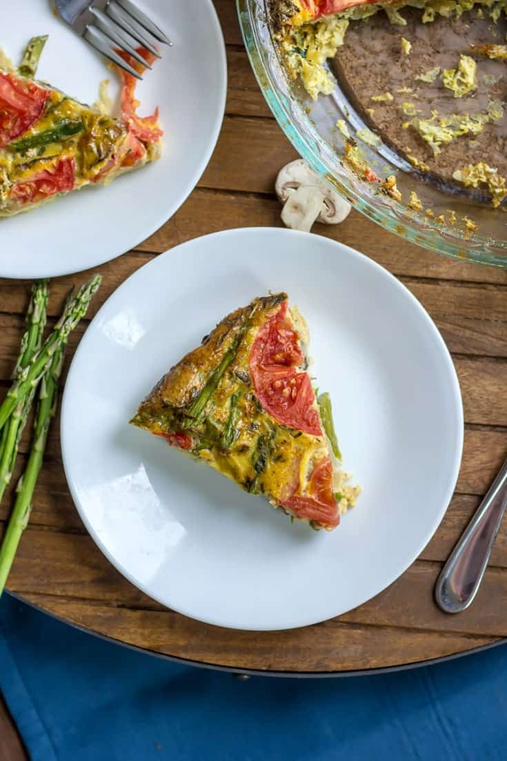 Mushroom Asparagus Crustless Quiche with sliced tomato on white plate