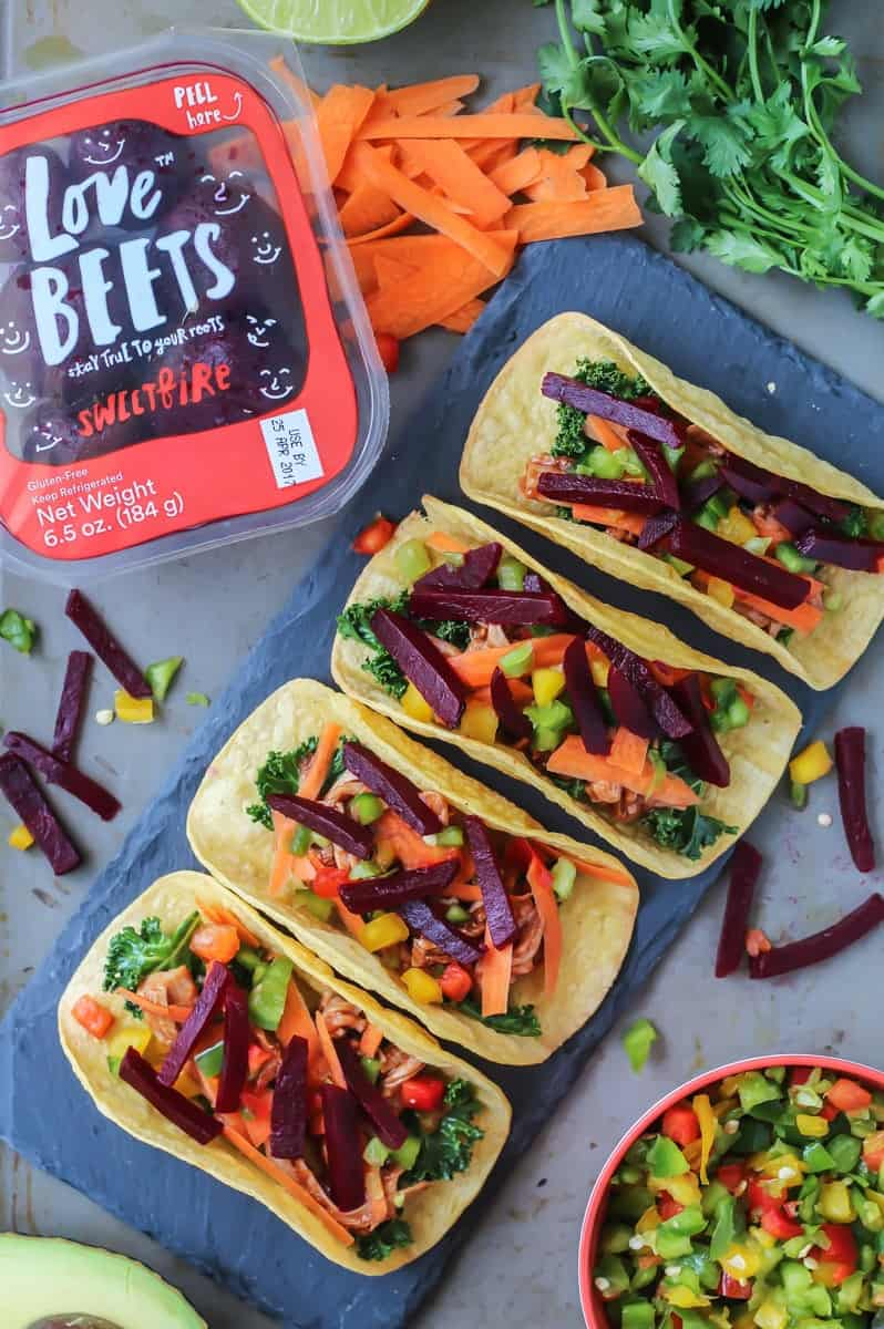 spicy beet pork tacos with love beets packaging and peeled carrots, cilantro, lime