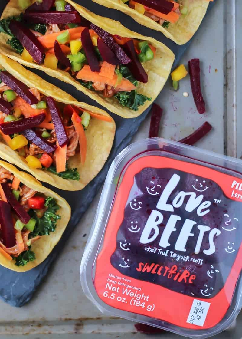BBQ Pork Tacos in a row on baking sheet with love beets in packaging