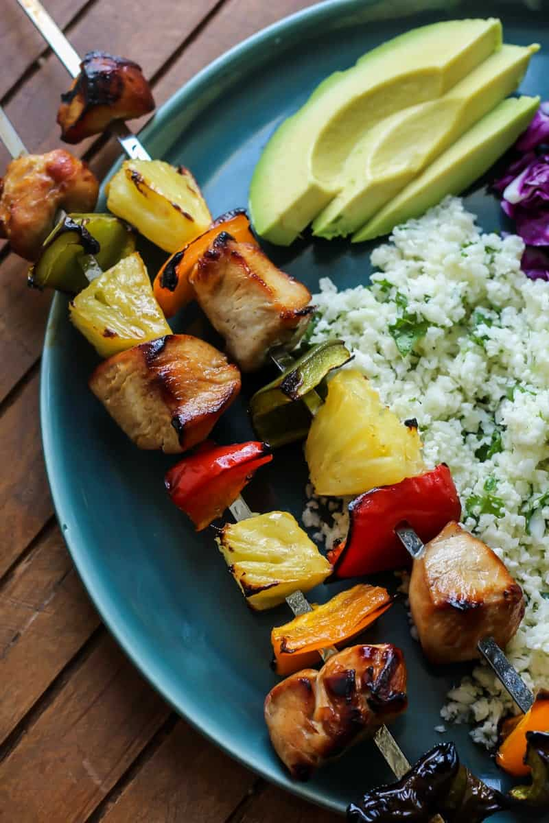 Citrus Herb Chicken Kebabs with Cilantro Lime Cauliflower Rice and avocado on teal plate