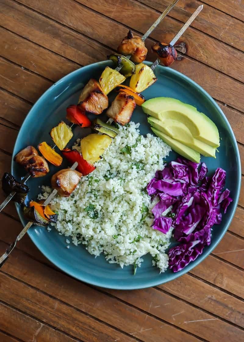 Chicken Kebabs and Cilantro Lime Cauliflower Rice with avocado on teal plate