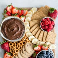 charcuterie board of cookies, pretzels, graham crackers, banana slices, raspberries, blueberries and strawberries with healthy chocolate fruit dip