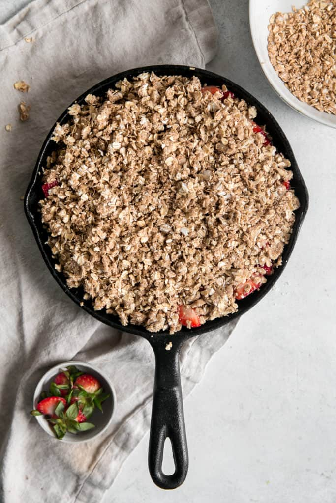 un baked oat topping in skillet with strawberries