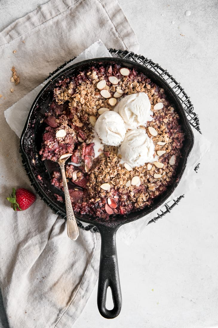strawberry crisp in skillet with ice cream and spoon