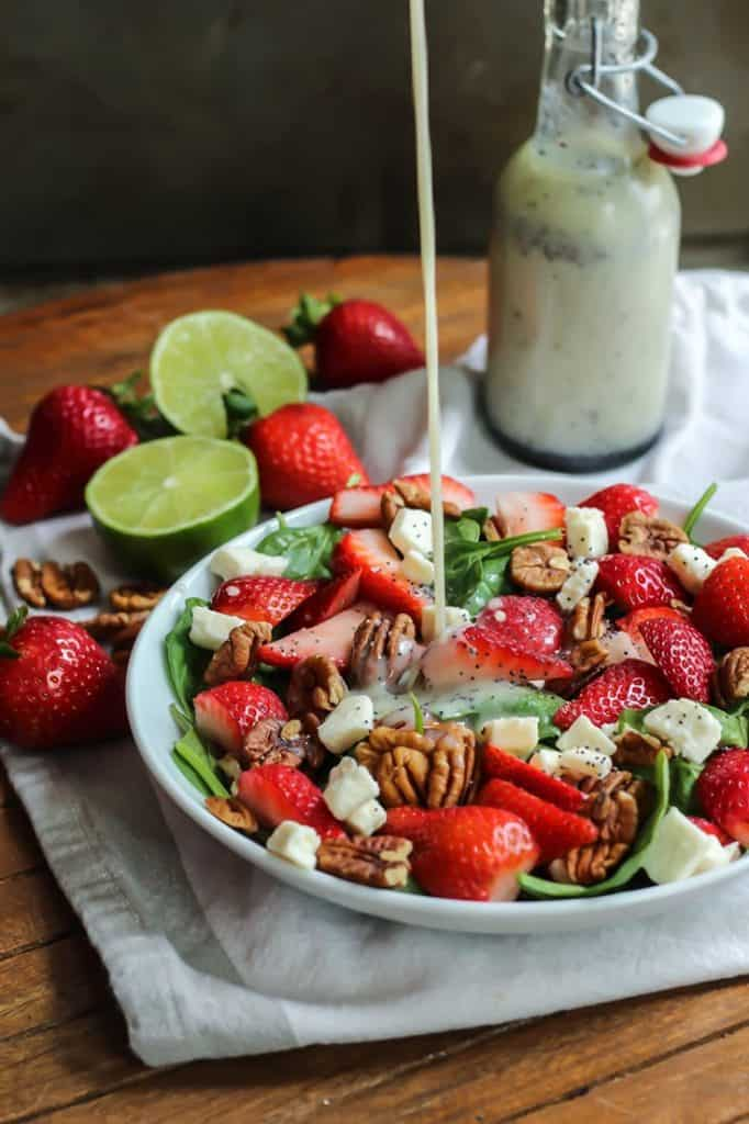 strawberry poppy seed salad with feta chunks and pecans in white bowl