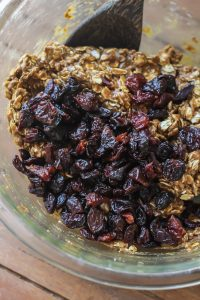 Dried cherries and cookie batter in a clear bowl